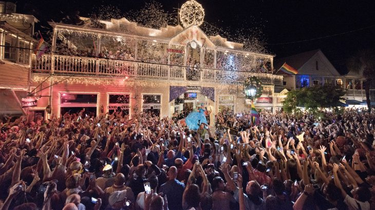 """Duval Street in Key West, Florida is jammed with revelers outside the Bourbon St. Pub early Sunday, January 1, 2017. Thousands watched female impersonator, Gary Marion (C) as """"Sushi,"""" descend in an oversized women's red high-heel shoe.  The Red Shoe Drop is a Key West New Year's Eve tradition and is one of four Florida Keys warm-weather takeoffs on New York City's Times Square ball drop marking the arrival of the new year.  / AFP PHOTO / Florida Keys News Bureau / Rob O'Neal"""