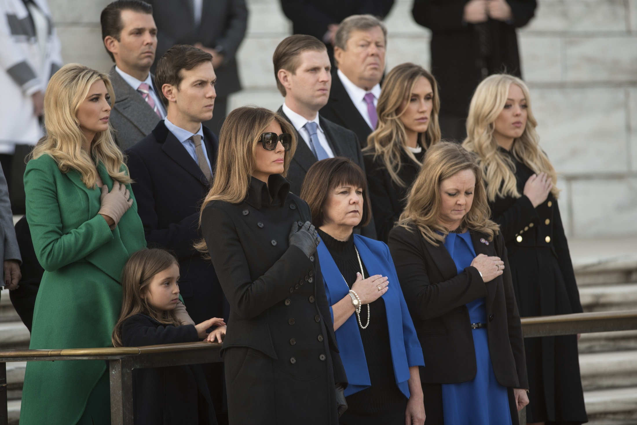 Family member watch as US President-elect Donald Trump and Vice President-elect Mike Pence take part in a wreath-laying ceremony at Arlington National Cemetery in Arlington, Virginia on January 19, 2017 / AFP PHOTO / MANDEL NGAN