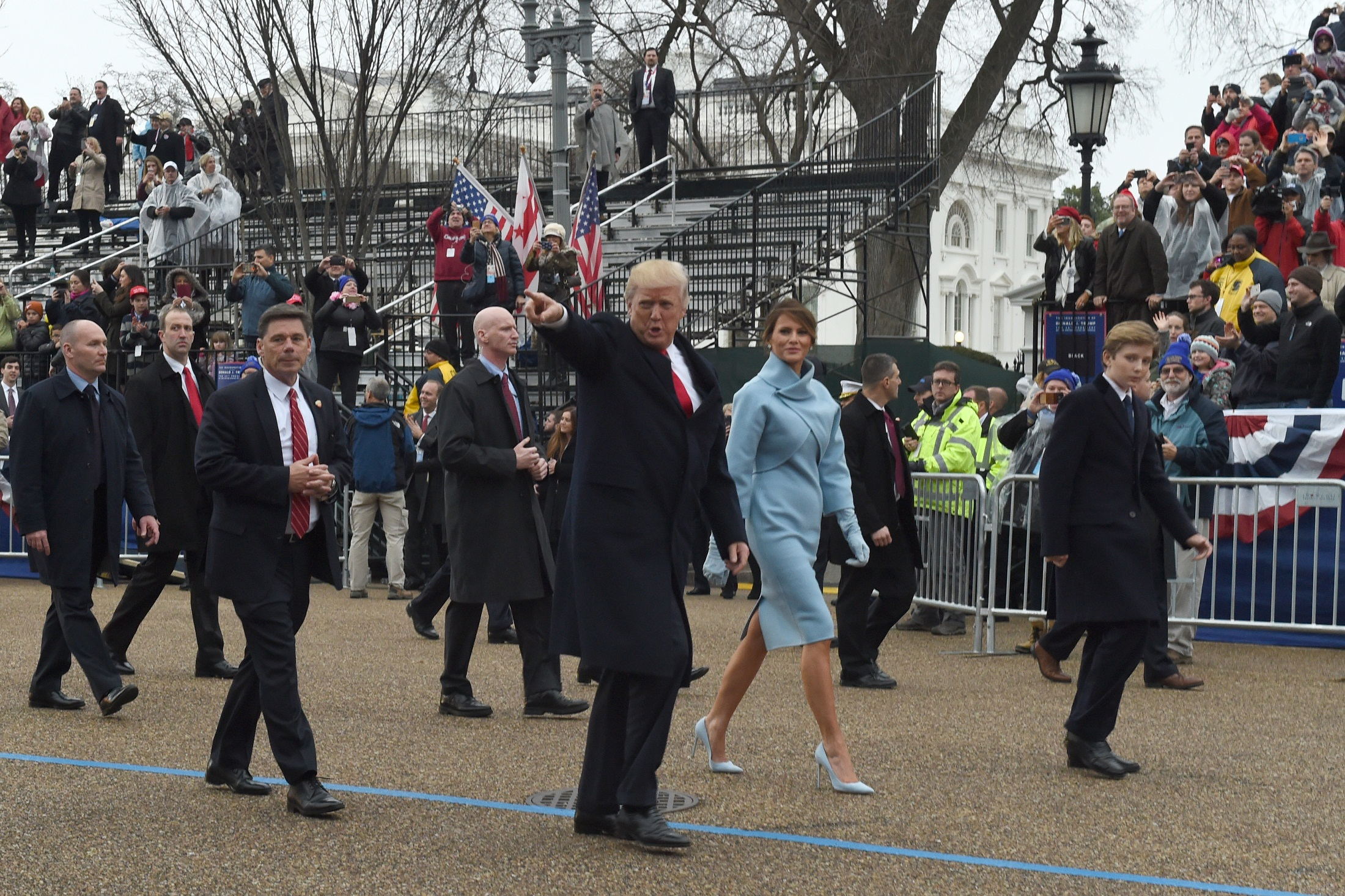 US President Donald Trump walks his son Barron (R) and wife Melania surrounded by Secret Service officers at the White House as the presidential inaugural parade winds through the nation's capital on January 20, 2017 in Washington, DC. / AFP PHOTO / Timothy A. CLARY
