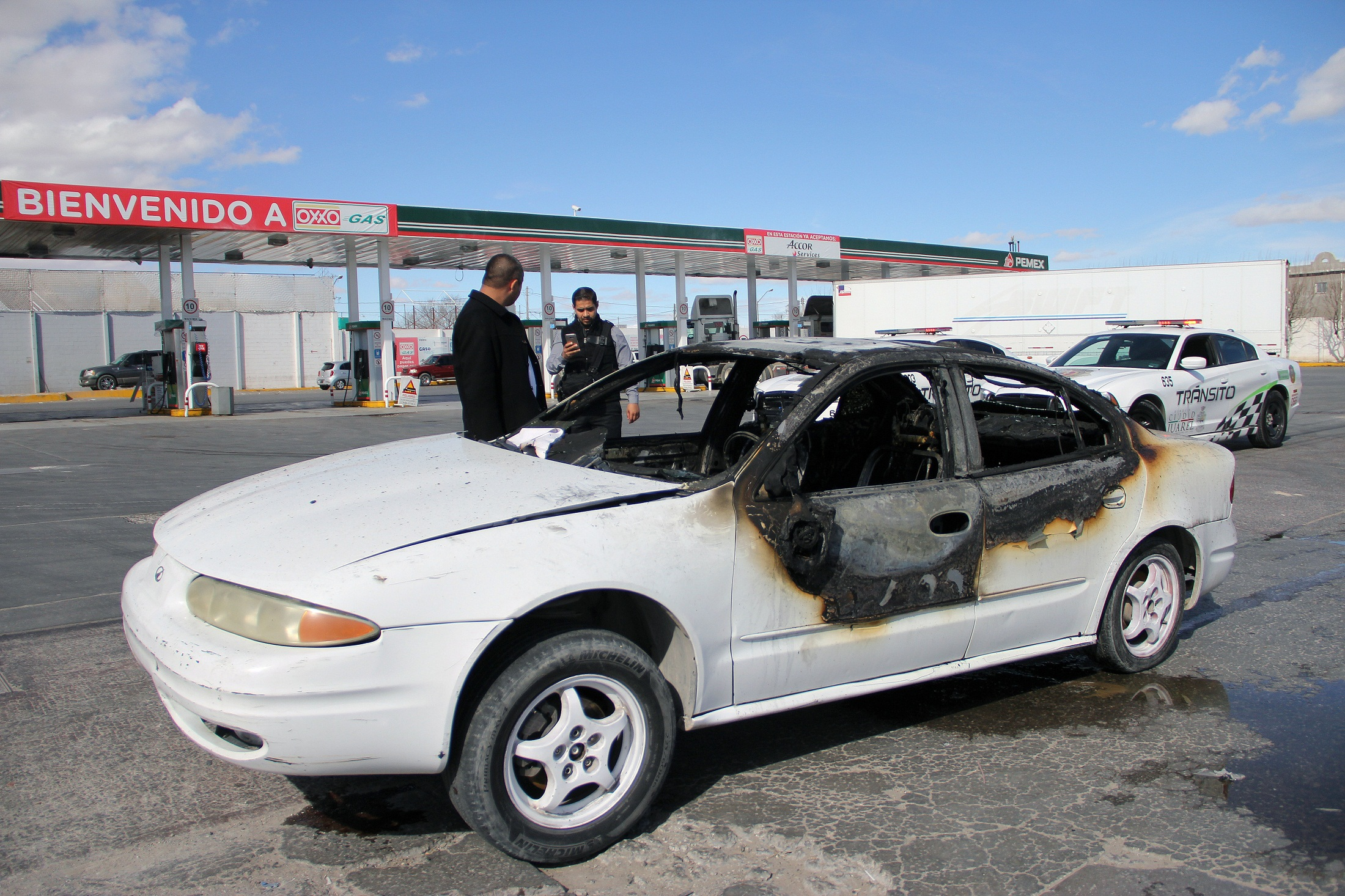 View of a burnt car in front of a gas station after a protest against the fuel price hikes in Ciudad Juarez, Chihuahua state, Mexico, on January 20, 2017.  On January 1, 2017 fuel prices in Mexico went up 20.1% for gasoline and 16.5% for diesel.  / AFP PHOTO / HERICKA MARTINEZ
