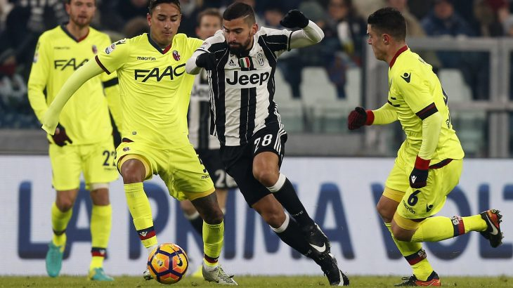 Bologna's defender Erick Pulgar from Chile (L) fights for the ball with Juventus' midfielder Tomas Rincon from Venezuela (C) during the Italian Serie A football match Juventus Vs Bologna on January 8, 2017 at the 'Juventus Stadium' in Turin.   / AFP PHOTO / MARCO BERTORELLO