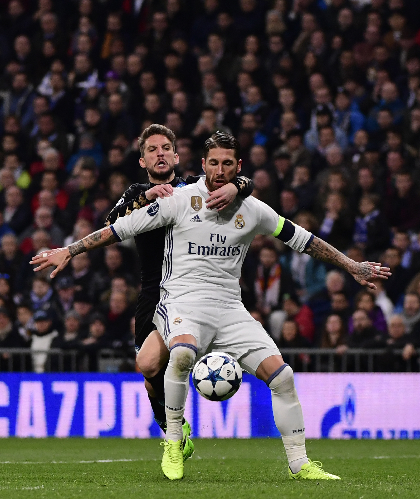 Napoli's forward from Belgium Dries Mertens (L) vies wth Real Madrid's defender Sergio Ramos during the UEFA Champions League round of 16 first leg football match Real Madrid CF vs SSC Napoli at the Santiago Bernabeu stadium in Madrid on February 15, 2017. / AFP PHOTO / PIERRE-PHILIPPE MARCOU