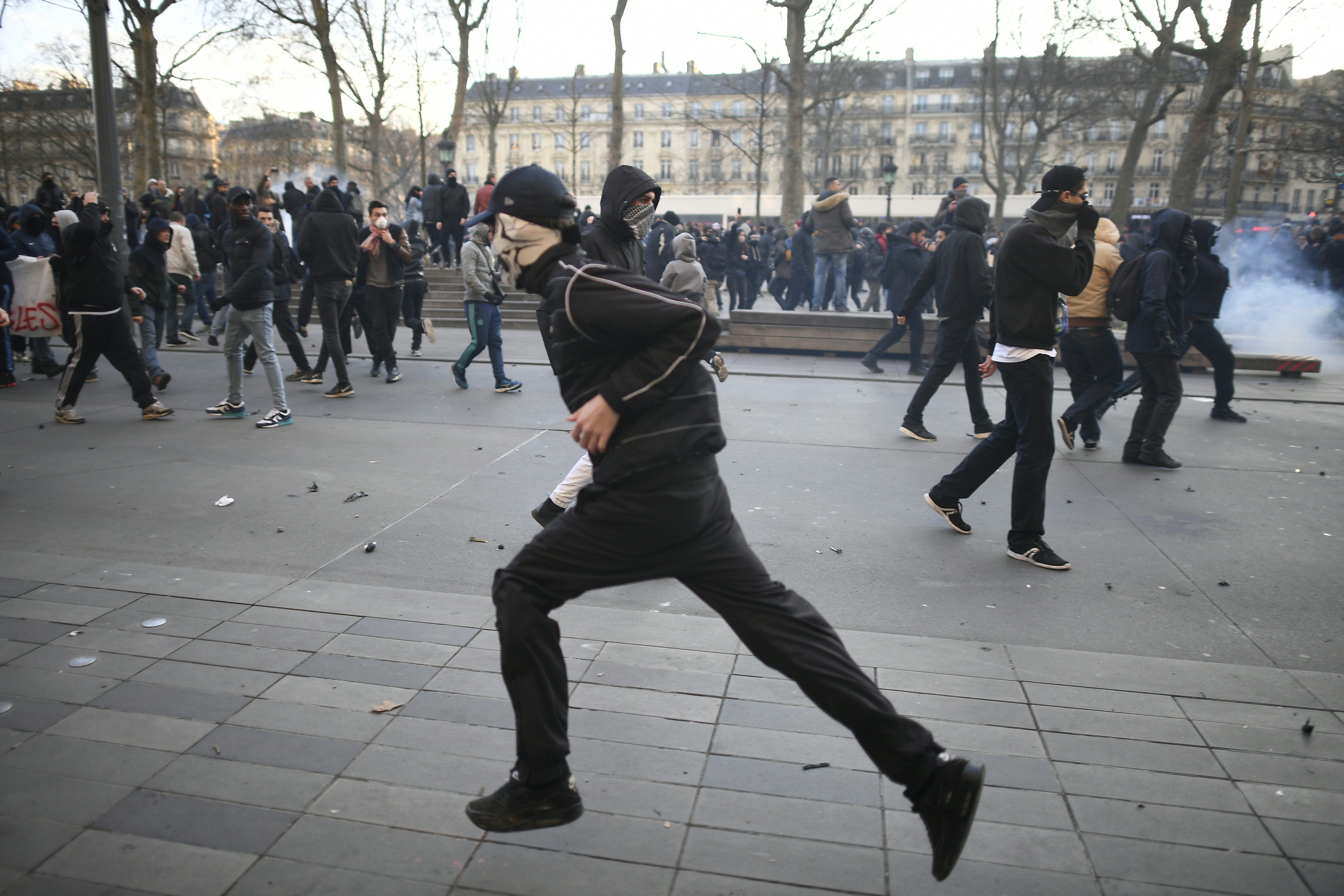 A person runs during a demonstration against police brutality on February 18, 2017 on the place de la Republique in Paris, following the alleged rape of a black youth, identified only as Theo, with a police baton, an incident that has sparked 10 nights of rioting and more than 200 arrests. The injuries sustained by Theo during a stop-and-search operation on February 2 in the suburb of Aulnay-sous-Bois, has revived long-simmering frustrations over policing in immigrant communities, where young men accuse the police of repeatedly targeting them in aggressive stop-and-search operations and using excessive force during arrests.  / AFP PHOTO / Lionel BONAVENTURE