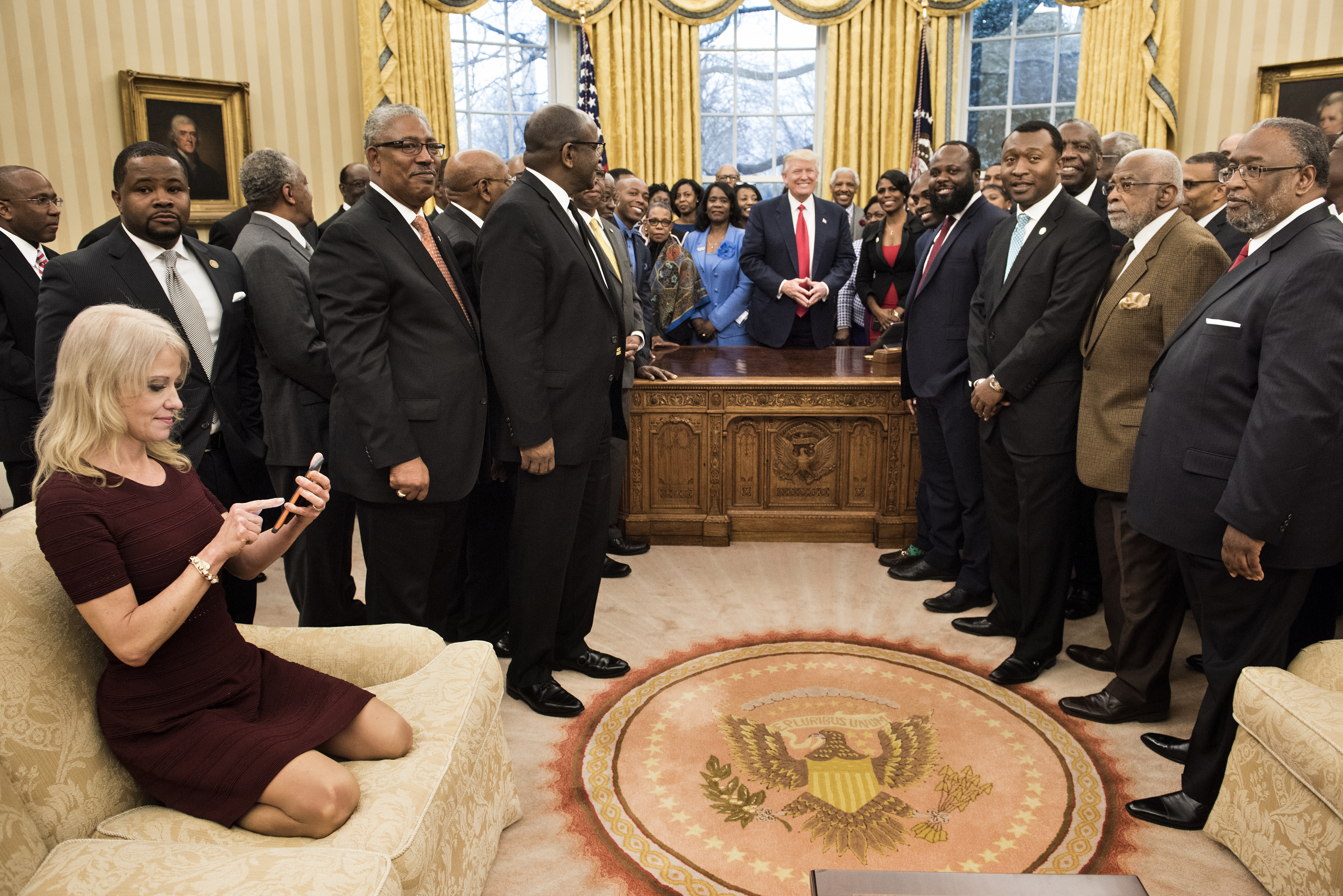 Counselor to the President Kellyanne Conway (L) checks her phone after taking a photo as US President Donald Trump and leaders of historically black universities and colleges pose for a group photo in the Oval Office of the White House before a meeting with US Vice President Mike Pence February 27, 2017 in Washington, DC. / AFP PHOTO / Brendan Smialowski