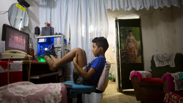 Kevin Lachaise, 8, watches a recorded TV show through the screen of a computer at the living room of his home in downtown Havana February 10, 2015. Netflix Inc launched its movie and TV streaming service in Cuba on Monday, joining the list of U.S. companies looking to take advantage of thawing diplomatic relations between the United States and the communist-ruled island country. REUTERS/Alexandre Meneghini (CUBA - Tags: BUSINESS MEDIA SCIENCE TECHNOLOGY) - RTR4P30W