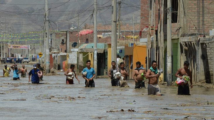 Local residents of the town of Huarmey, 300 kilometres north of Lima, wade through muddy water in the street on March 19, 2017 after a flash flood hit the evening before. The El Nino climate phenomenon is causing muddy rivers to overflow along the entire Peruvian coast, isolating communities and neighbourhoods. Thousands have been affected since January, and 72 people have died. Most cities face water shortages as water lines have been compromised by mud and debris. / AFP PHOTO / CRIS BOURONCLE